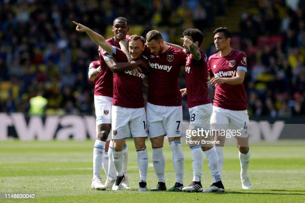 Mark Noble of West Ham United celebrates with teammates after scoring his team's first goal during the Premier League match between Watford FC and...