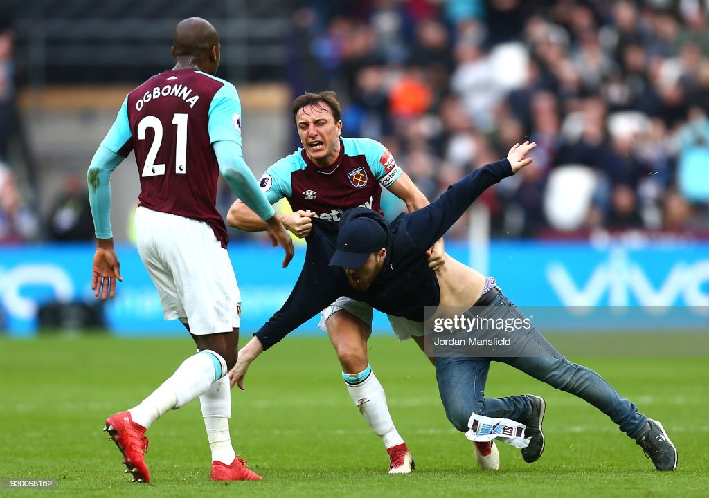 Mark Noble of West Ham United clashes with a pitch invader during the Premier League match between West Ham United and Burnley at London Stadium on March 10, 2018 in London, England.