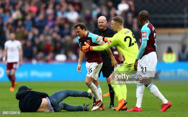 Mark Noble of West Ham United clashes with a pitch invader during the Premier League match between West Ham United and Burnley at London Stadium on...