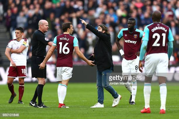 Mark Noble of West Ham United confronts a pitch Invader during the Premier League match between West Ham United and Burnley at London Stadium on...