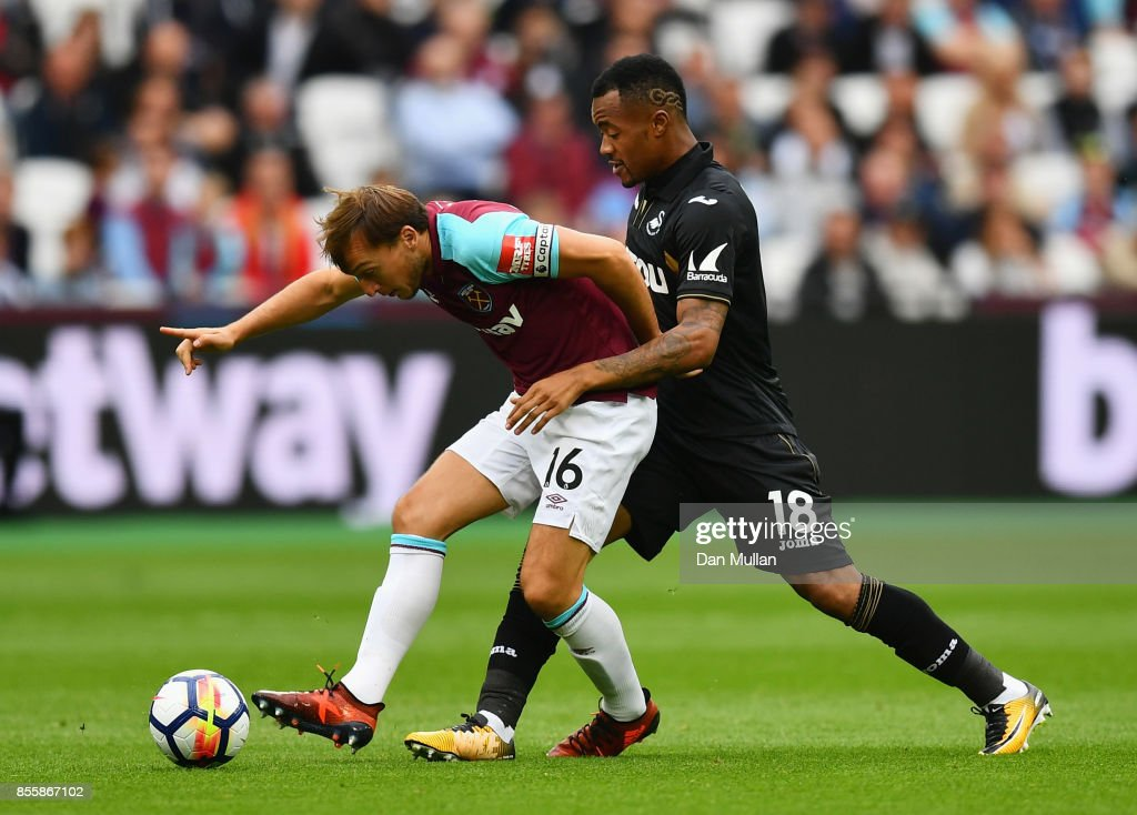 Mark Noble of West Ham United controls the ball under pressure of Jordan Ayew of Swansea City during the Premier League match between West Ham United and Swansea City at London Stadium on September 30, 2017 in London, England.