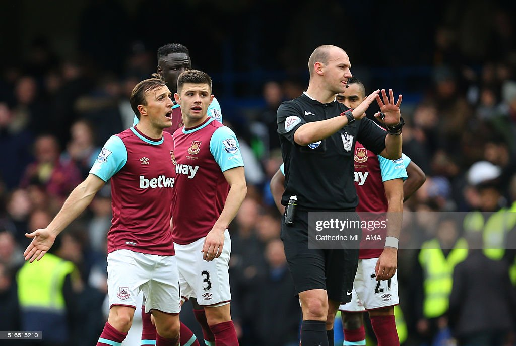 Mark Noble of West Ham United has words with Referee Robert Madley as the teams walk off for half time during the Barclays Premier League match between Chelsea and West Ham United at Stamford Bridge on March 19, 2016 in London, England.