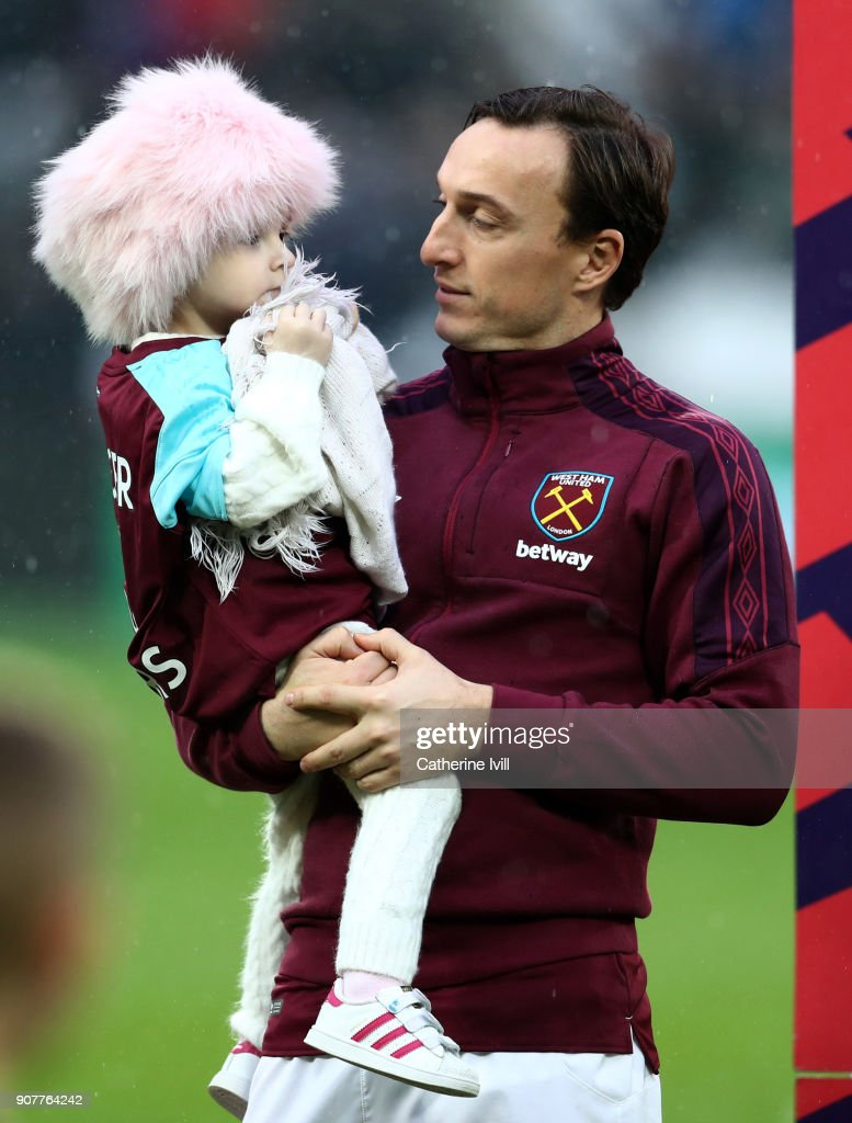 Mark Noble of West Ham United holds Isla Caton as he lines up prior to the Premier League match between West Ham United and AFC Bournemouth at London Stadium on January 20, 2018 in London, England.
