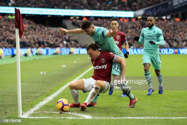 Mark Noble of West Ham United holds off Sead Kolasinac of Arsenal during the Premier League match between West Ham United and Arsenal FC at London...