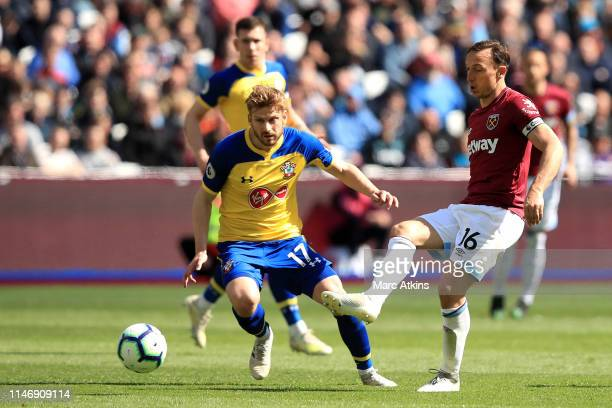 Mark Noble of West Ham United is challenged by Stuart Armstrong of Southampton during the Premier League match between West Ham United and...
