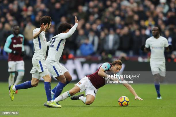 Mark Noble of West Ham United is challenged by Willian of Chelsea and Cesc Fabregas of Chelsea during the Premier League match between West Ham...