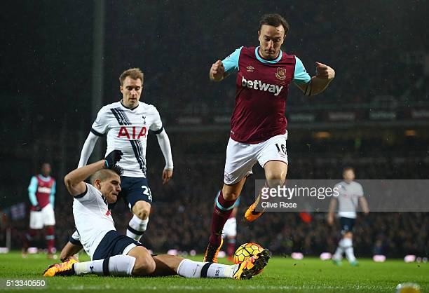Mark Noble of West Ham United jumps a challenge from Erik Lamela of Tottenham Hotspur during the Barclays Premier League match between West Ham...