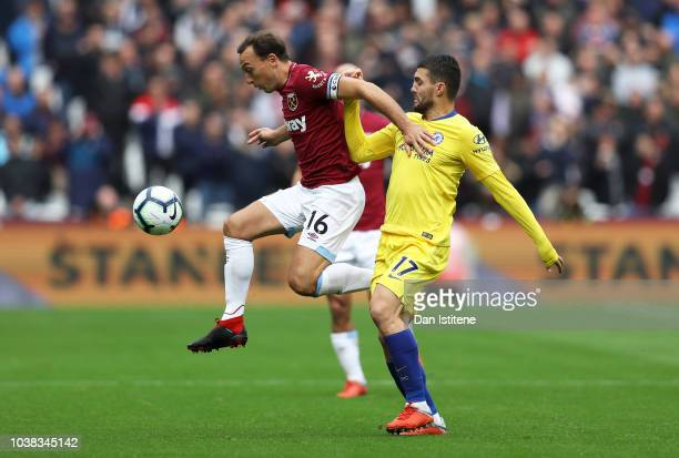 Mark Noble of West Ham United jumps for the ball under pressure from Mateo Kovacic of Chelsea during the Premier League match between West Ham United...