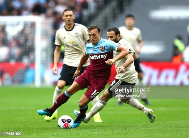 Mark Noble of West Ham United moves away from Juan Mata of Manchester United during the Premier League match between West Ham United and Manchester...