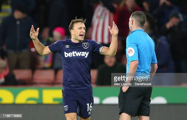 Mark Noble of West Ham United protests to referee Michael Oliver after the Premier League match between Sheffield United and West Ham United at...