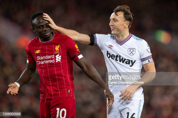 Mark Noble of West Ham United shares a joke with Sadio Mane of Liverpool during the Premier League match between Liverpool FC and West Ham United at...