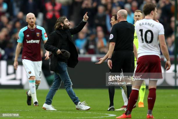 Mark Noble of West Ham United speaks with a pitch invader during the Premier League match between West Ham United and Burnley at London Stadium on...