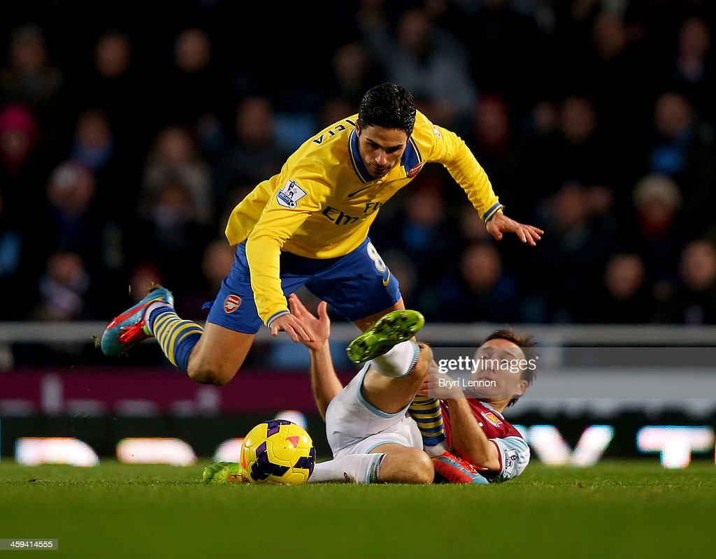 Mark Noble of West Ham United tackles Mikel Arteta of Arsenal during the Barclays Premier League match between West Ham United and Arsenal at Boleyn Ground on December 26, 2013 in London, England.