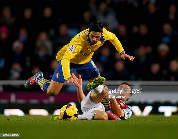 Mark Noble of West Ham United tackles Mikel Arteta of Arsenal during the Barclays Premier League match between West Ham United and Arsenal at Boleyn...
