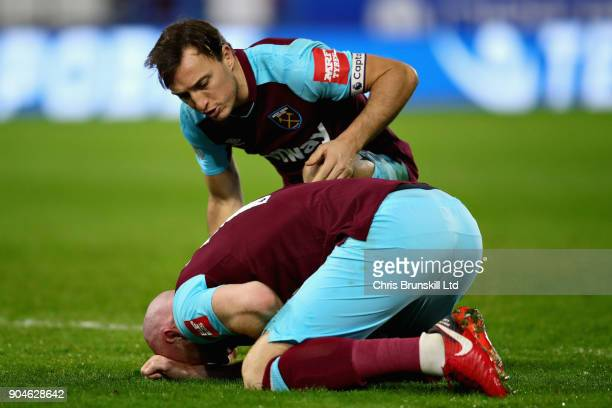 Mark Noble of West Ham United talks with teammate James Collins after a collision during the Premier League match between Huddersfield Town and West...