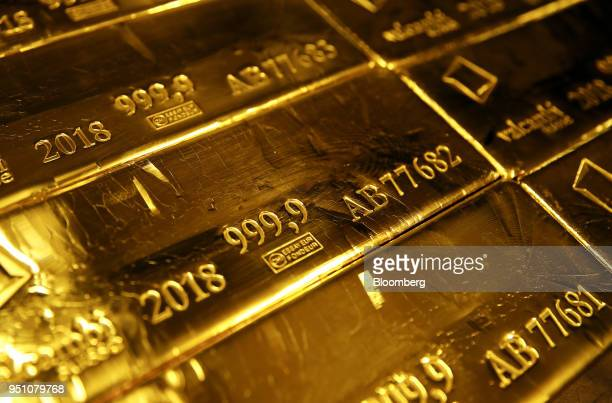 A mark of 9999 fine sits on hallmarked 125 kilogram gold bullion bars stacked at the Valcambi SA precious metal refinery in Lugano Switzerland on...