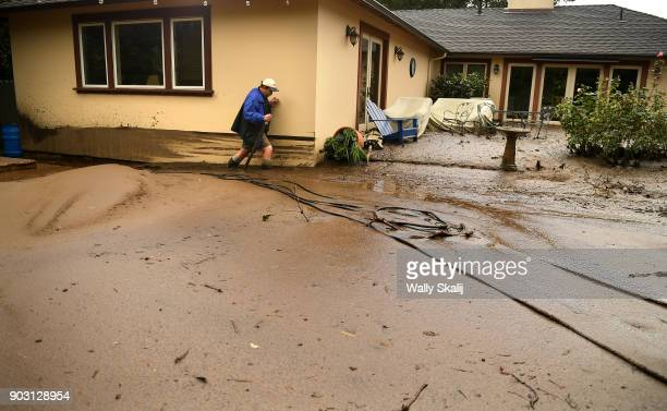Mark Olson tries to access his house as he climbs through mud in his back yard along Olive Mill Road in Montecito after a major storm hit the burn...