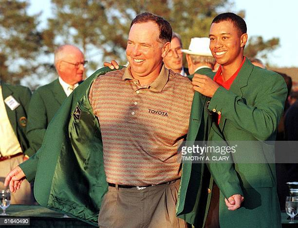Mark O'Meara gets the Green Jacket from Tiger Woods the defending Masters champion 12 April at Augusta National Golf Course in Augusta GA O'Meara...
