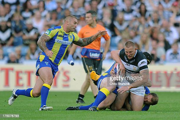 Mark O'Meley of Hull FC is tackled by Micky Higham and Chris Hill of Warrington Wolves during the Tetley's Challenge Cup Semi Final between Hull FC...