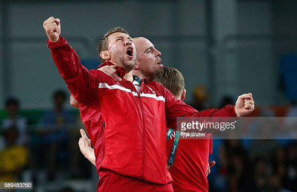 Mark Overgaard Madsen of Denmark and coaches celebrate after defeating Peter Bacsi of Hungary during the Men's 75 kg GrecoRoman Wrestling semifinals...