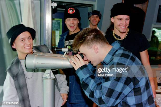 Mark Owen, Howard Donald, Gary Barlow, Robbie Williams and Jason Orange of Take That looking through a telescope in Tokyo, March 1993