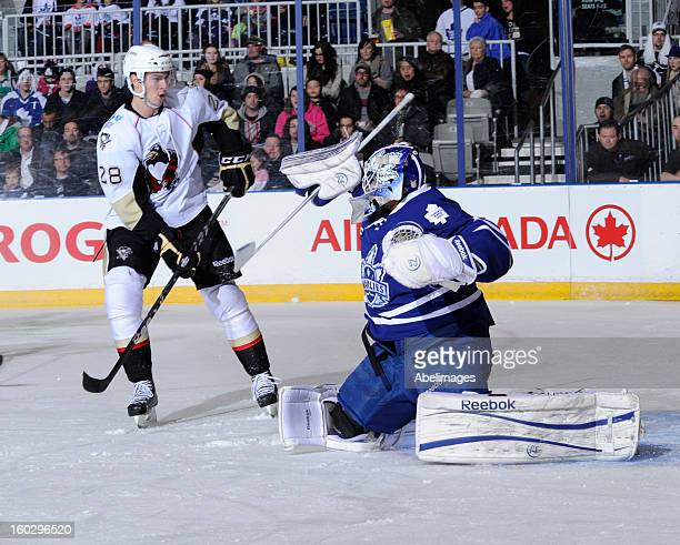 Mark Owuya of the Toronto Marlies makes a save while Adam Payerl of the WilkesBarre Scranton Penguins looks for a rebound during game action on...