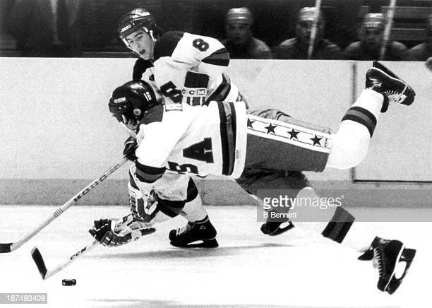 Mark Pavelich of Team USA trips as he passes the puck to his teammate Dave Silk during an 1980 exhibition game against the Soviet Union on February...