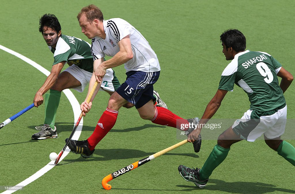 Mark Pearn (C) of Britain manoeuvres past Abdul Haseem Khan (L) and Shafqat Rasool (R) of Pakistan during their first round match of the men's hockey Champions Trophy in Auckland on December 3, 2011. Britain beat Pakistan 2-1. AFP PHOTO / Michael BRADLEY