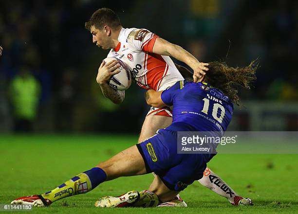 Mark Percival of St Helens is tackled by Ashton Sims of Warrington Wolves during the First Utility Super League Semi Final match between Warrington...