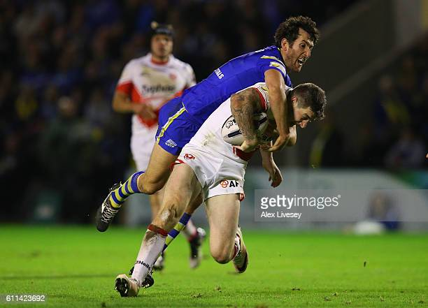 Mark Percival of St Helens is tackled by Stefan Ratchford of Warrington Wolves during the First Utility Super League Semi Final match between...