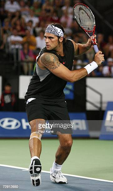 Mark Philippoussis of Australia attempts to play on after injuring his lower right leg during the Hopman Cup Group A match between Australia and...