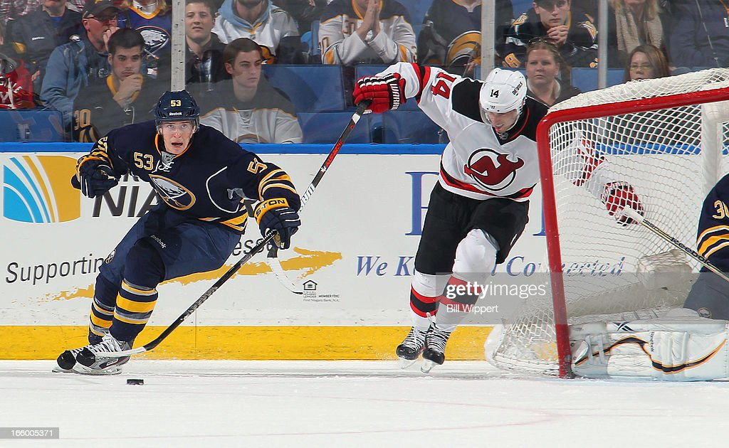Mark Pysyk #53 of the Buffalo Sabres rounds the net while pursued by Adam Henrique #14 of the New Jersey Devils on April 7, 2013 at the First Niagara Center in Buffalo, New York. Buffalo defeated New Jersey, 3-2.