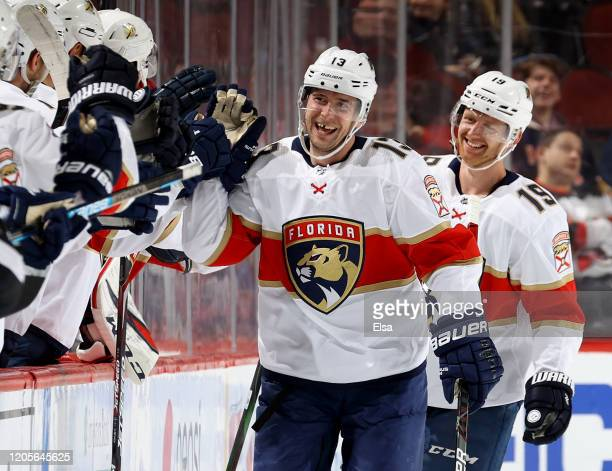 Mark Pysyk of the Florida Panthers celebrates his goal with teammates on the bench as Mike Matheson joins in the second period against the New Jersey...