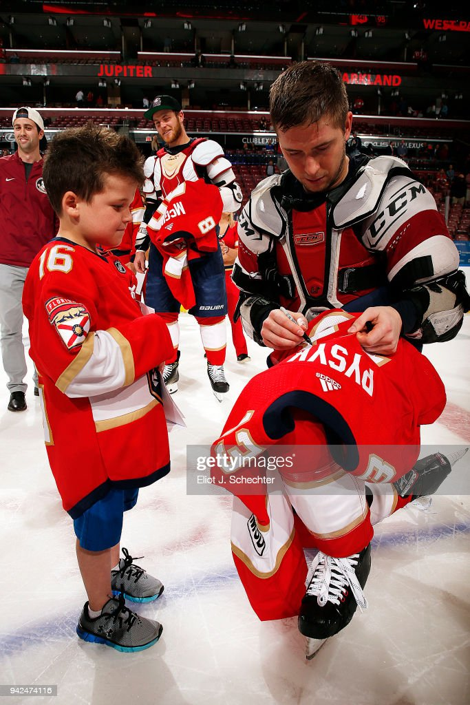 Mark Pysyk #13 of the Florida Panthers signs his game worn jersey for a fan after their win against the Boston Bruins at the BB&T Center on April 5, 2018 in Sunrise, Florida.