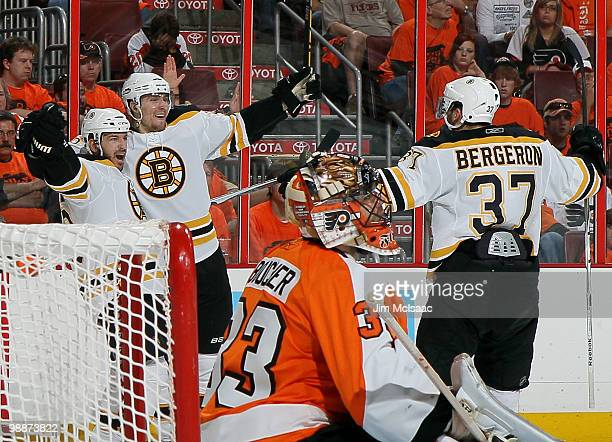 Mark Recchi of the Boston Bruins celebrates his third period goal with teammates Blake Wheeler and Patrice Bergeron as Brian Boucher of the...