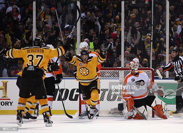 Mark Recchi of the Boston Bruins celebrates with teammates after he scored a third period goal to tie the game 11 against goalie goalie Michael...