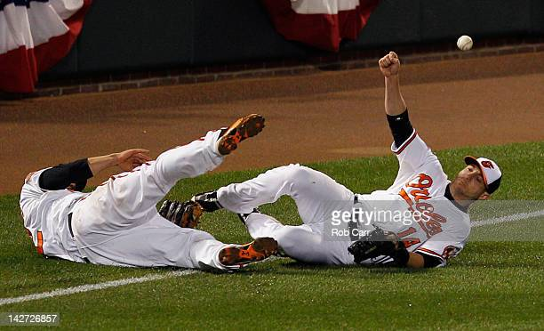 Mark Reynolds and Nolan Reimold of the Baltimore Orioles miss a double hit by Mark Teixeira of the New York Yankees during the tenth inning of the...