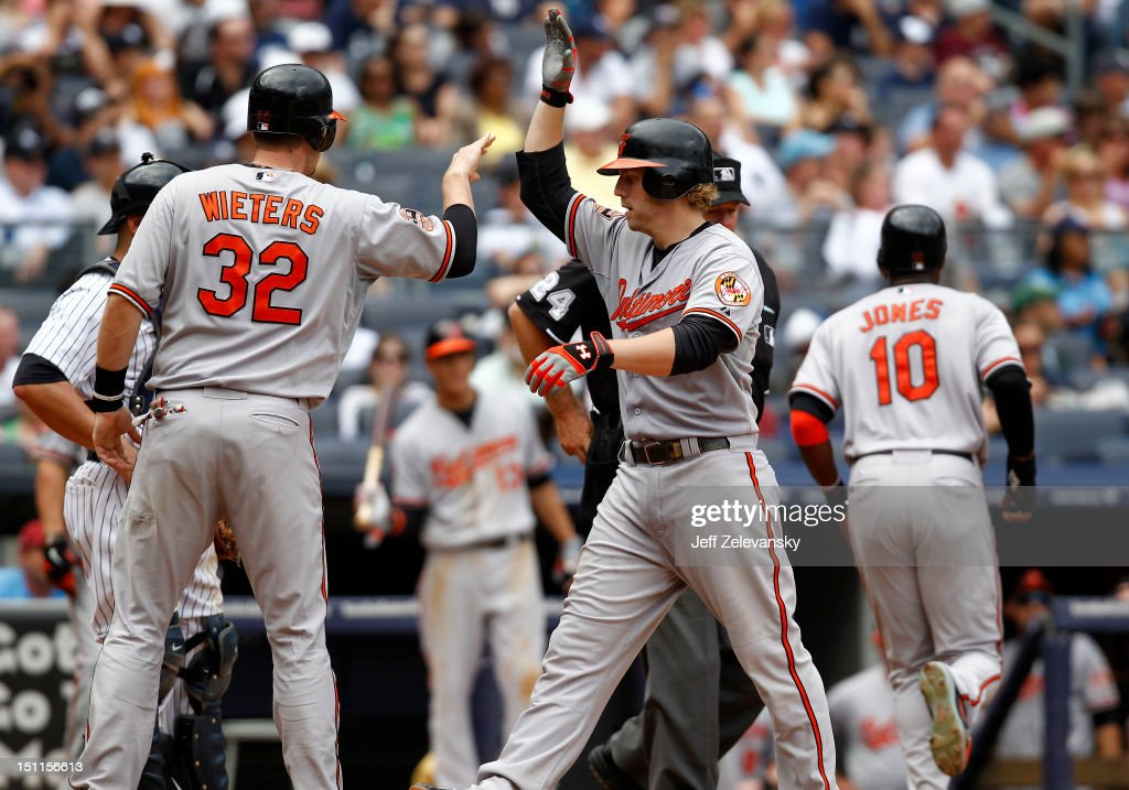 Mark Reynolds #12 is greeted by Matt Wieters #32 of the Baltimore Orioles of the Baltimore Orioles after his three-run home run against the New York Yankees at Yankee Stadium on September 2, 2012 in the Bronx borough of New York City.