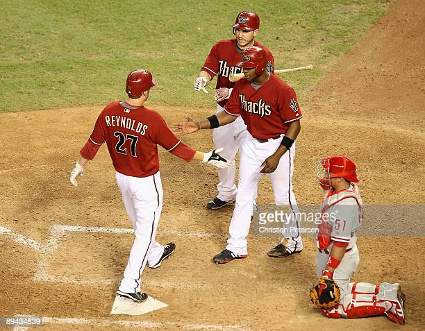 Mark Reynolds of the Arizona Diamondbacks is congratulated by teammates Justin Upton and Miguel Montero after hitting a 2 run home run against the...