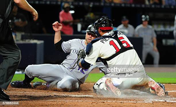 Mark Reynolds of the Colorado Rockies is tagged out at home by A J Pierzynski of the Atlanta Braves at Turner Field on July 16 2016 in Atlanta Georgia
