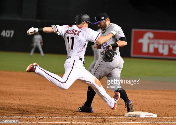 Mark Reynolds of the Colorado Rockies makes a play on a one hop throw as AJ Pollock of the Arizona Diamondbacks is forced out at first base during...
