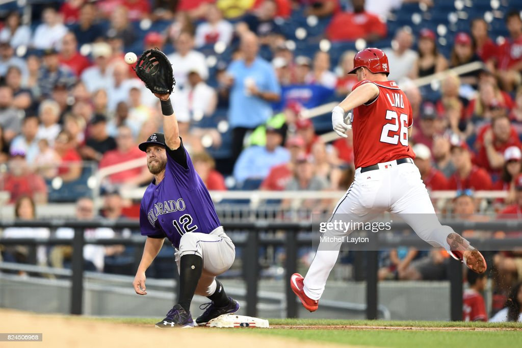 Mark Reynolds #12 of the Colorado Rockies makes the catch to get Adam Lind #26 of the Washington Nationals at first base in the third inning during game two of a doubleheader of a baseball game at Nationals Park on July 30, 2017 in Washington, DC.