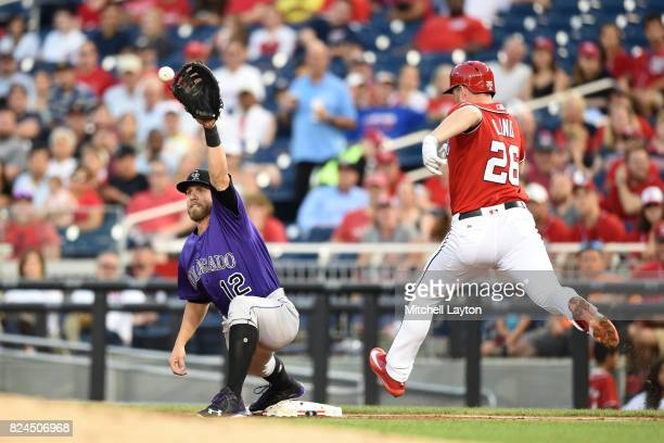 Mark Reynolds of the Colorado Rockies makes the catch to get Adam Lind of the Washington Nationals at first base in the third inning during game two...