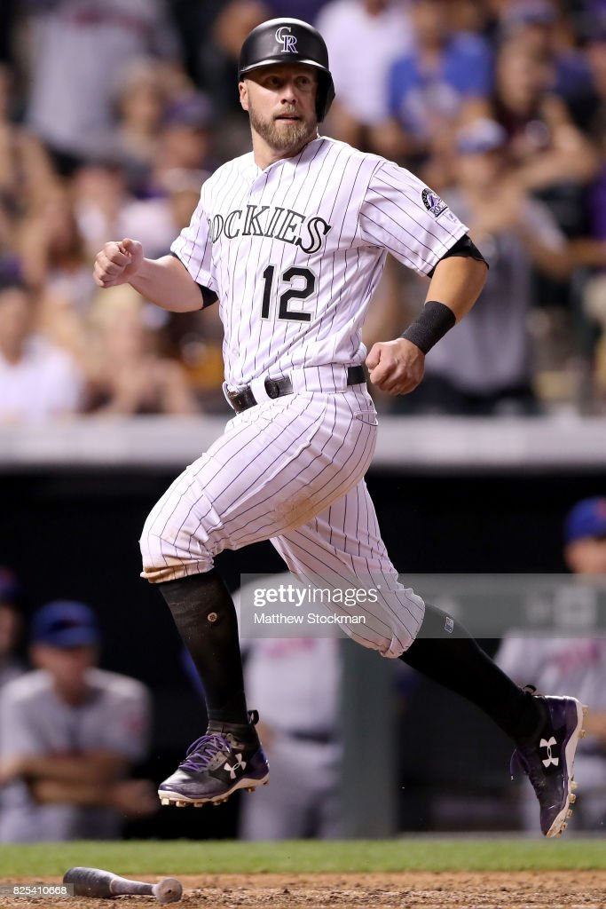 Mark Reynolds #12 of the Colorado Rockies scores on a Carlos Gonzalez single in the eighth inning against the New York Mets at Coors Field on August 1, 2017 in Denver, Colorado.