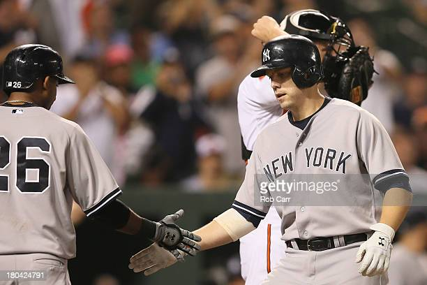 Mark Reynolds of the New York Yankees is congratulated by Eduardo Nunez after hitting a two RBI home run against the Baltimore Orioles during the...