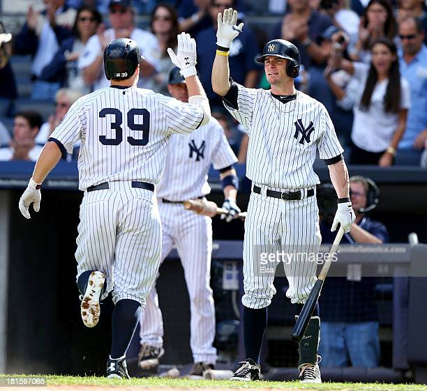 Mark Reynolds of the New York Yankees is congratulated by teammate Chris Stewart after Reynolds hit a solo home run in the third inning against the...
