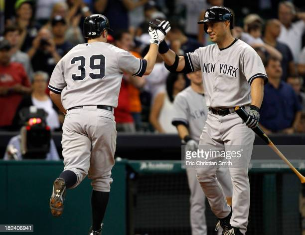 Mark Reynolds of the New York Yankees is congratulated by teammate Travis Hafner after Reynolds hit a solo home run during the fourteenth inning...