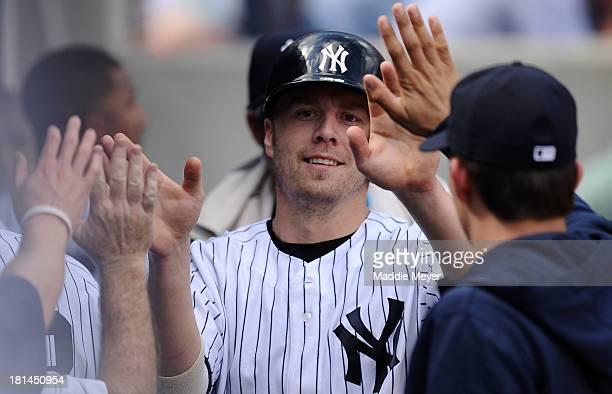 Mark Reynolds of the New York Yankees is congratulated by teammates after scoring a run in the third inning against the San Francisco Giants during...