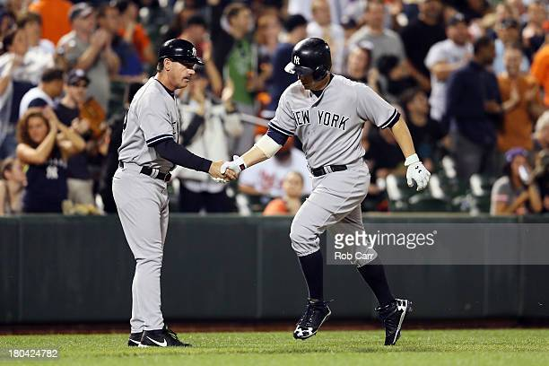 Mark Reynolds of the New York Yankees is congratulated by third base coach Rob Thomson after hitting a two RBI home run against the Baltimore Orioles...