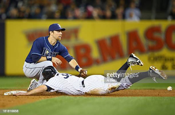 Mark Reynolds of the New York Yankees slides safely into second base as the ball gets away from Ben Zobrist of the Tampa Bay Rays during their game...